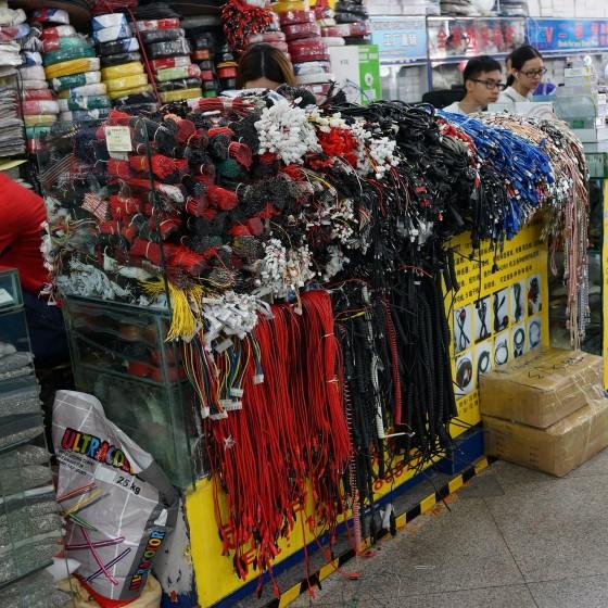 華強北路電気街 無造作に積み上げられた部品類 と 部品のネット販売に専念する店員たち